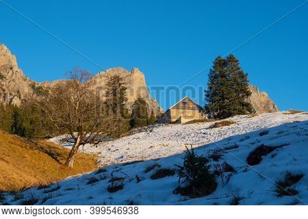An Alpine Mountain Hut In Front Of Swiss Peaks On A Late Autumn Afternoon