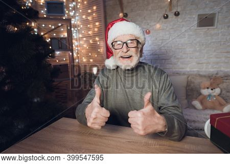 Grandfather Is Sitting Near Cristmas Tree In Santa Claus's Hat At Night At Home.