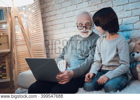 Grandfather And Grandson Look At The Laptop While Sitting On The Bed. Grandson Smiled While Looking