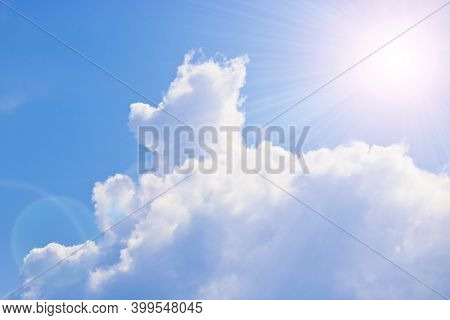 Cumulus And Cirrus Clouds And Bright Sunbeams Against The Blue Sky. Atmospheric Phenomenon, Weather,