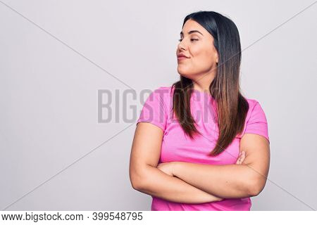 Young beautiful brunette woman wearing casual pink t-shirt standing over white background looking to the side with arms crossed convinced and confident