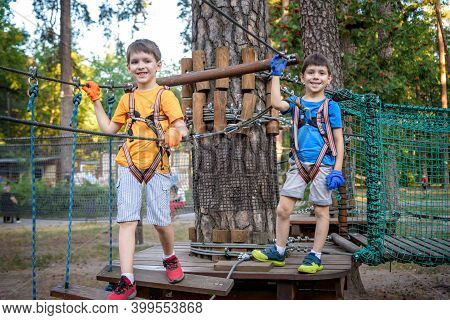 Two Cute Happy Young Children, Boy And His Brother In Protective Harness, Carbine And Safety Helmets