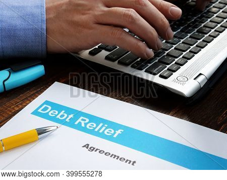 Debt Relief Agreement Papers And Man With Laptop.