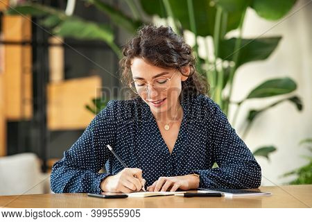 Smiling young woman wearing spectacles and writing on book with pencil. Beautiful girl taking notes on agenda. University student sitting on table and writing an idea.