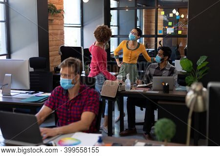Diverse colleagues wearing face masks discussing at desk in casual office. man in face mask using lasptop at desk in foreground. hygiene in workplace during coronavirus covid 19 pandemic.