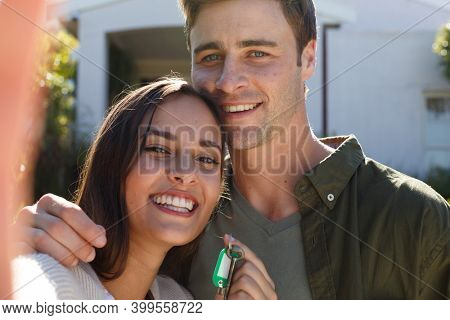Portrait of caucasian couple holding house keys and smiling to camera. self isolation in new home during covid 19 coronavirus pandemic.