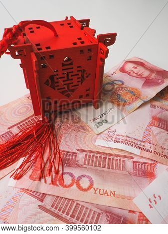 Miniature Chinese Pavilion In Bright Red Standing On Chinese 100 Renminbi Banknotes Against A White
