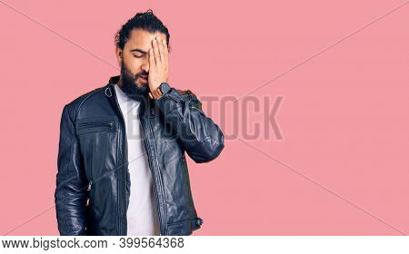 Young arab man wearing casual leather jacket yawning tired covering half face, eye and mouth with hand. face hurts in pain.
