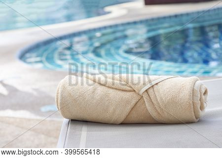 Folded Towels Are Placed On A Chair Next To The Swimming Pool.