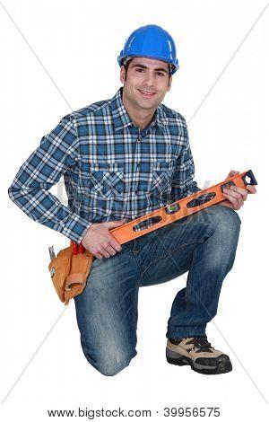 Builder knelt holding spirit level