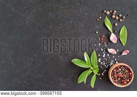 Fresh Bay Leaf, Allspice, Pink Peppercorn, Garlic On Dark Stone Background With Copy Space. Top View