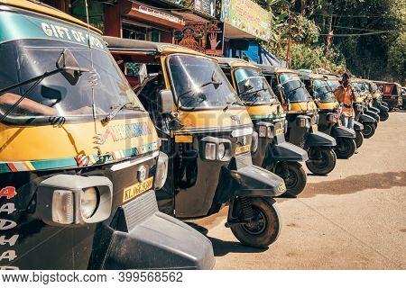 Munnar, India - January 30, 2020: A row of parked colorful tuk-tuk auto rickshaws in Munnar, Kerala, India