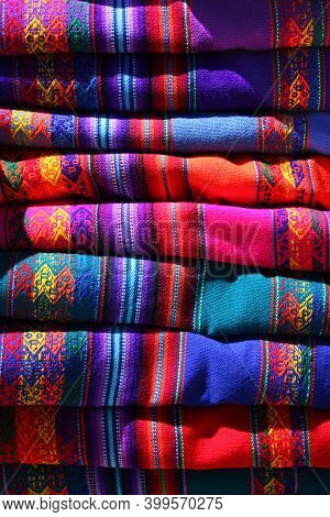 Detail Of Peruvian Indigenous Blankets Stacked For Sale, With Indigenous Geometric Drawings And Blue