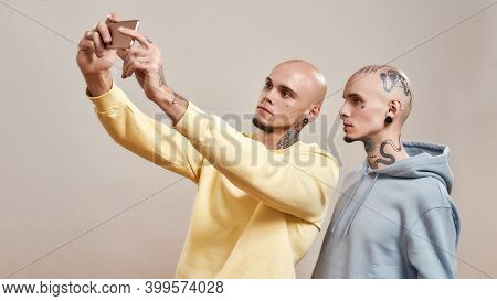 Two Young Caucasian Twin Brothers In Casual Wear With Tattoos And Piercings Taking Selfie On Mobile