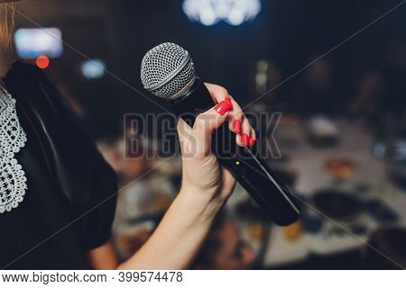 Microphone And Unrecognizable Female Singer Close Up. Cropped Image Of Female Singer In Pink Dress ,