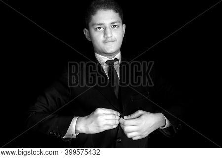 Half Length Shot Of A Young Businessman Closing His Coat's Buttons Isolated On A Black Background.