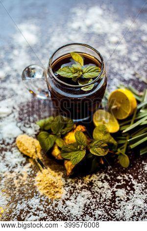 Shot Of Ayurvedic Kada Or Immunity Drink On Brown Surface Consisting Of Lemongrass,lemon,mint Leaves