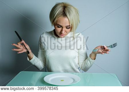 Sick Girl With Anorexia Sits At The Table With A Knife And Fork. Woman Sits At The Table And Looks A