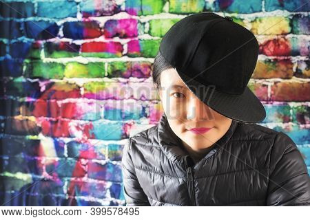 A Chinese Woman Posing Against A Color Brick Background Wearing A Jacket And Baseball Hat To The Sid