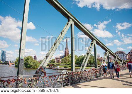 Frankfurt, Germany - June 12, 2019: River view of The Eiserner Steg. The Eiserner Steg is a pedestrian bridge in Frankfurt am Main built in 1868. City skyline in Frankfurt, Germany.