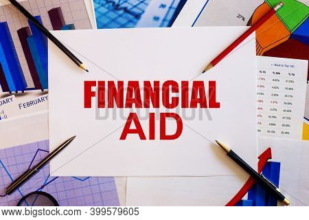 Financial Aid Is Written On A White Background Near Colored Graphs, Pens And Pencils. Business Conce