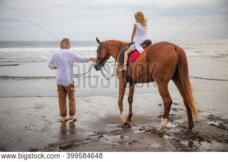 Little Girl On A Horse. Father Leading Horse By Its Reins On The Beach. Horse Riding By The Sea. Fam