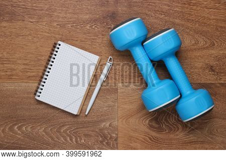 Plan Your Future Workouts. Drawing Up A Training Program. Notebook With Pen And Dumbbell On The Floo
