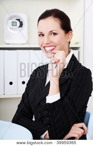 Attractive businesswoman holding home keys. Real estae concept.