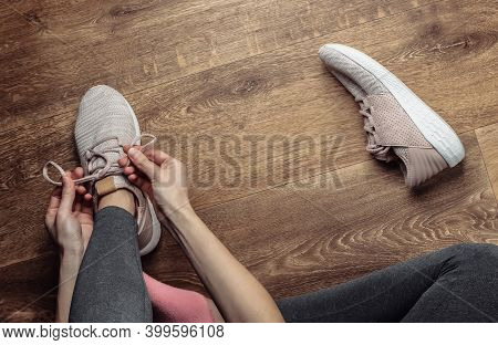 Fitness, Sport Concept. Woman Tying Shoelaces Of Sports Shoes For Running While Sitting On The Floor