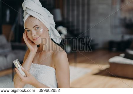 Skin Care Procedure Concept. Adorable Healthy Woman Applies Face Lotion, Takes Care Of Her Skin, Wra