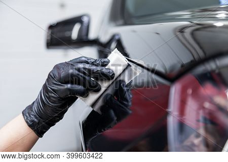 The Process Of Applying A Nano-ceramic Coating On The Car's Fender By A Male Worker With A Sponge An
