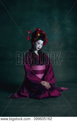 Humble. Young Japanese Woman As Geisha Isolated On Dark Green Background. Retro Style, Comparison Of