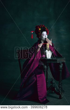 Tasty Noodles. Young Japanese Woman As Geisha Isolated On Dark Green Background. Retro Style, Compar