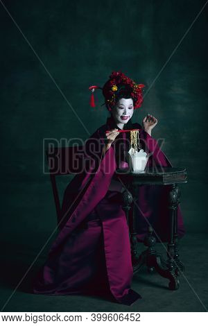 Appetizer. Young Japanese Woman As Geisha Isolated On Dark Green Background. Retro Style, Comparison