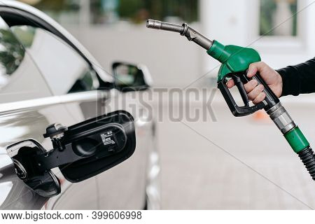 Cropped Shot Of Mans Hand Pumping Gasoline Fuel In Car At Gas Station. Auto Being Filled With Petrol