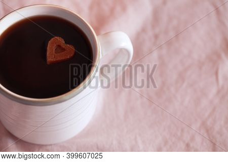White Cup Of Coffee With Heart Shaped Sugar On Pink Textile Background. Concept Of Love. Copy Space