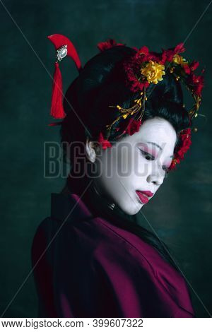 Inspiration. Young Japanese Woman As Geisha Isolated On Dark Green Background. Retro Style, Comparis