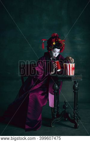 Movie Food. Young Japanese Woman As Geisha Isolated On Dark Green Background. Retro Style, Compariso