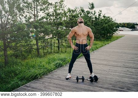 Healthy Muscular Man Stands With Naked Torso, Raises Head Above And Breathes Deeply, Wears Sport Clo