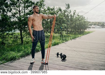 Full Length Shot Of Strong Bearded Sportsman Flexes Muscles With Elastic Resistance Band, Wears Spor