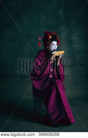 Biting Fish Hot-dog. Young Japanese Woman As Geisha Isolated On Dark Green Background. Retro Style,