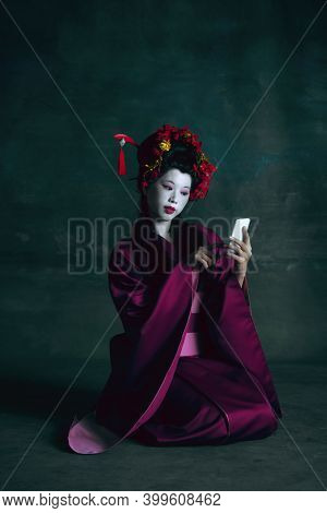 Selfie Time. Young Japanese Woman As Geisha Isolated On Dark Green Background. Retro Style, Comparis