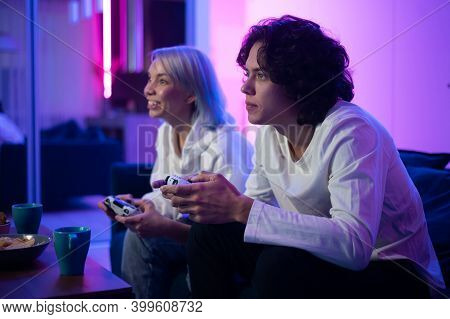 Couple Of Young Adults Playing Video Games At Home. Emotional Diverse Gamers Holding Joysticks And C