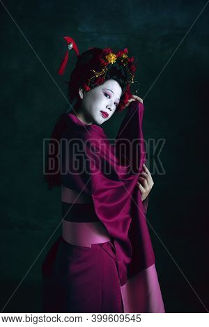 Dreamful. Young Japanese Woman As Geisha Isolated On Dark Green Background. Retro Style, Comparison