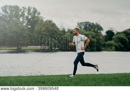 Sporty European Man Dressed In T Shirt, Trousers And Sneakers And Runs Along River, Trains Outdoors,