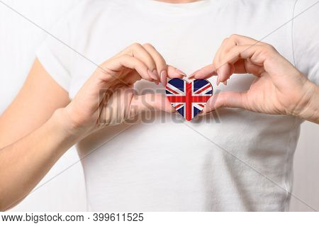 Love Great Britain. The Girl Holds A Heart In The Form Of The Flag Of Great Britain On Her Chest. Br