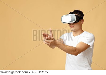 Online Game With Modern Devices And Virtual World. Serious Young Zoomer Student Man In Vr Glasses Sh