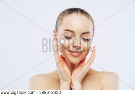 Close Up Shot Of Young Adult Woman With Naked Shoulders Applies Nourishing Moisturising Cream For So