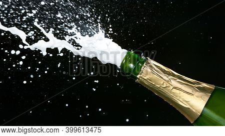 Champagne explosion with flying cork closure, opening champagne bottle closeup, celebration theme.