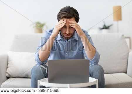 Concerned Businessman At Laptop Touching Head Having Business Problem Sitting On Sofa Indoors. Compu